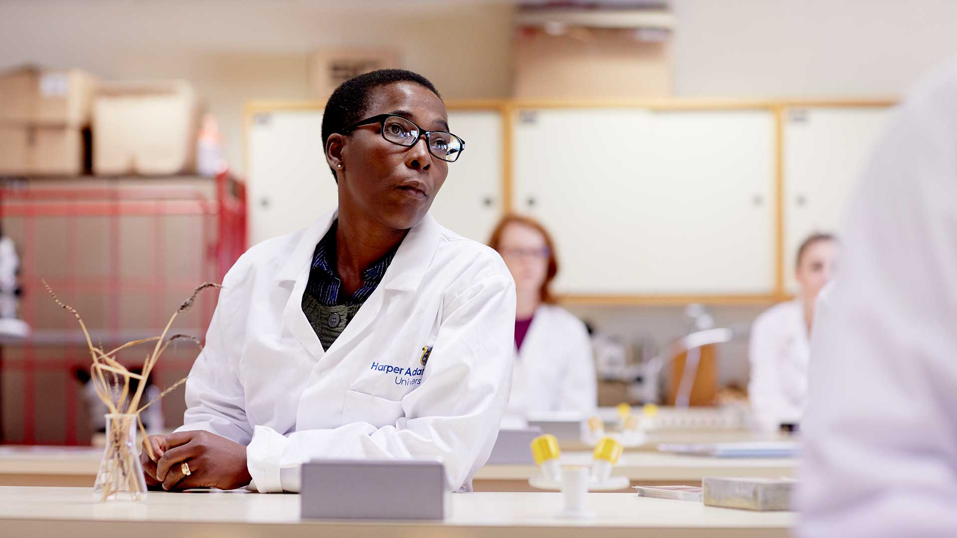 A black female student wearing glasses and a white lab coat, sitting in one of the science laboratories. Two other students can be seen in the background, but they are out of focus.