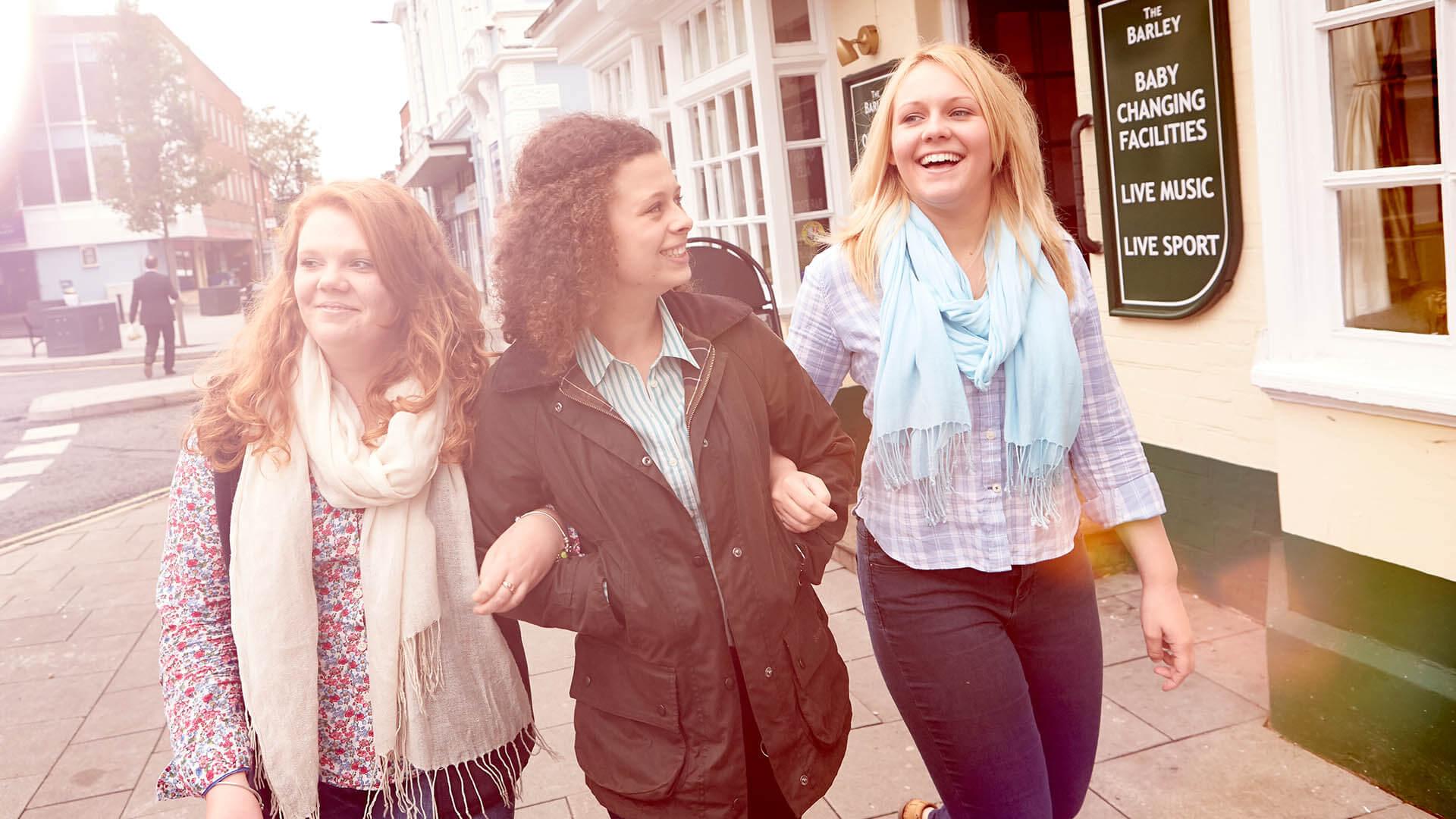 Three female students walk down Newport High Street in the sunshine