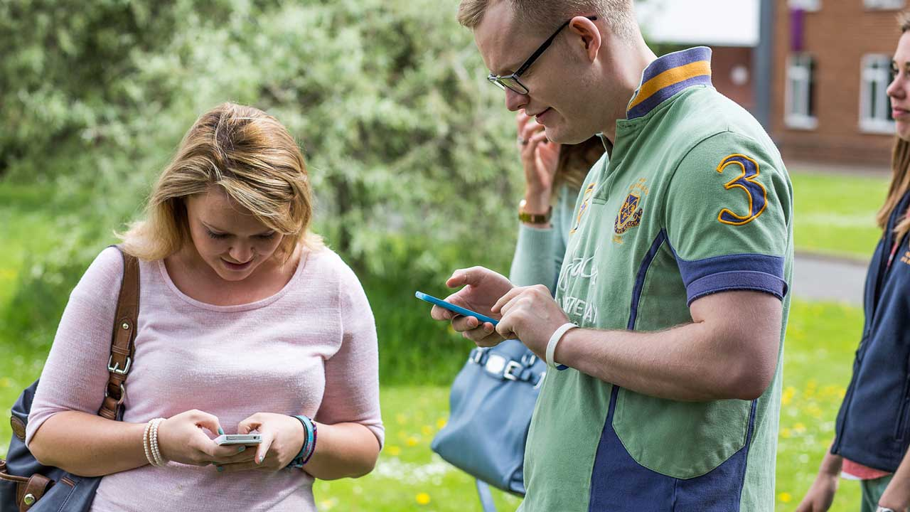 Students using mobile phones on campus
