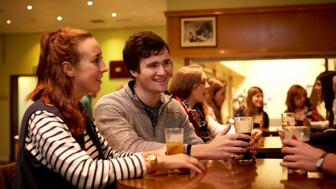 Image description: Students drinking in The Welly Inn on campus.